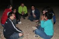 Reunidos en un camping a la luz de la luna hablando y contando historias.