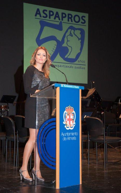 María del Mar en el atril del auditorio bajo el logo del 50 aniversario de ASPAPROS